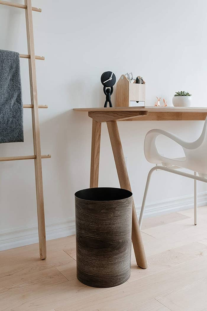 The Umbra Treela Small Trash Can with barn wood exterior finish in an office