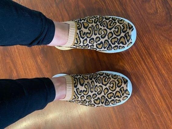 Reviewer wearing the mesh sneakers in cheetah print