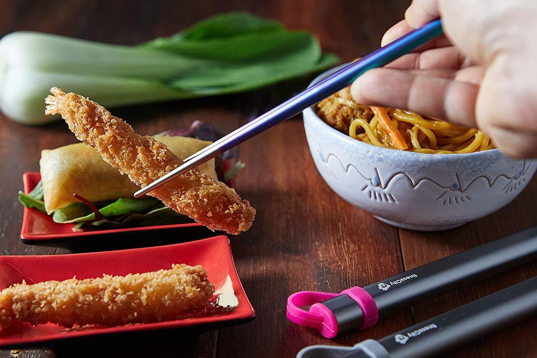 A person using the chopsticks to pick up a piece of tempura