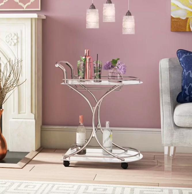 Silver bar cart with an upper and lower shelf covered in floral mixed drinks, bottles, and cocktail shakers