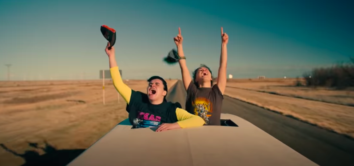 The teens yell in joy from a sunroof of a car