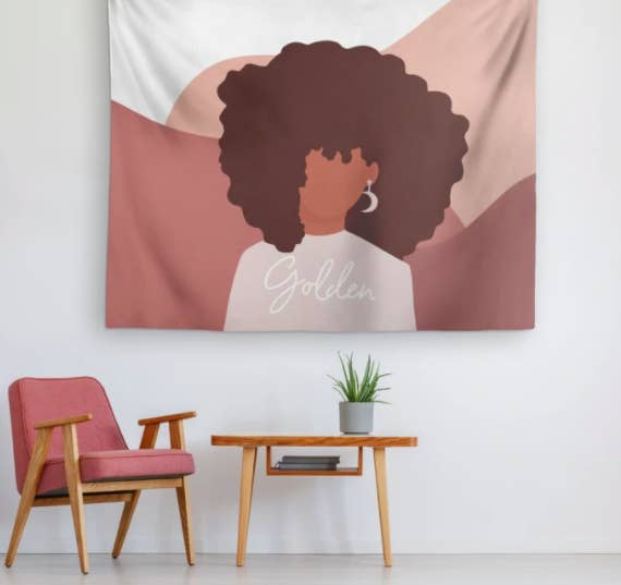 """Pink, brown, and white patterned tapestry with a woman wearing moon earrings and a shirt that says """"golden"""""""