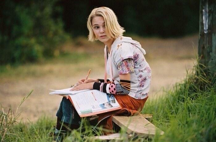 Leslie sitting on a wooden bench, doing her homework