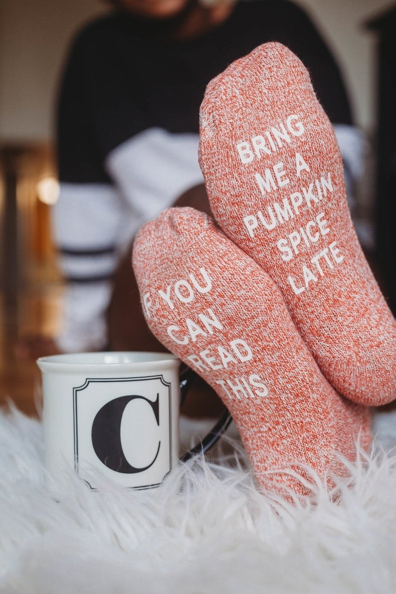 """A person showing the bottoms of the pink socks that say """"If you can read this bring me a pumpkin spice latte"""""""