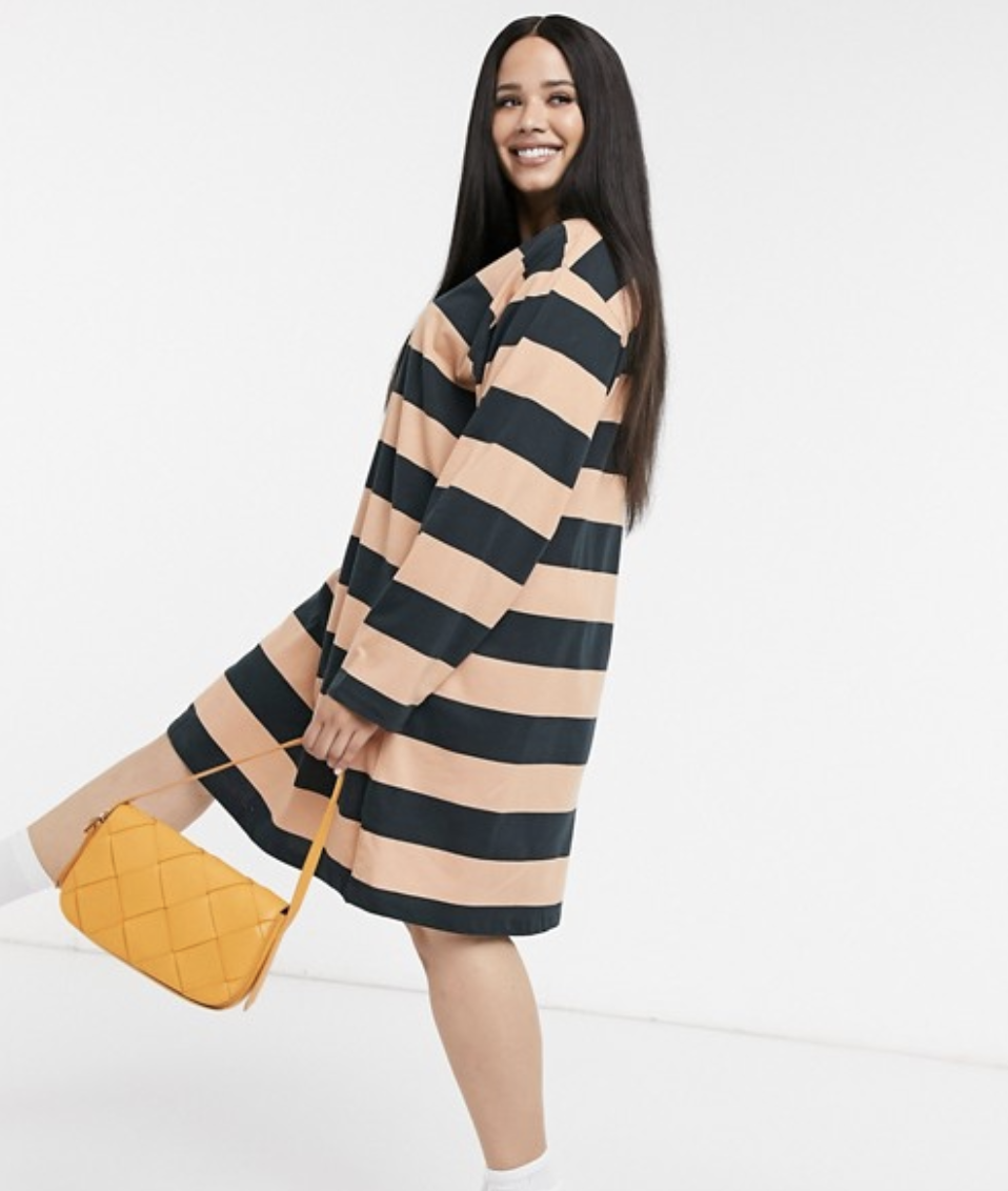 Model in a long-sleeved black and beige striped dress