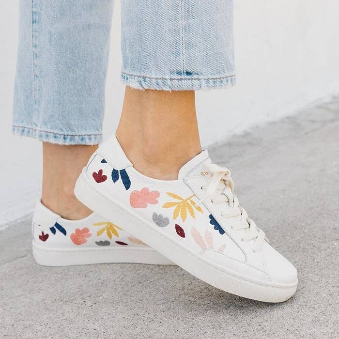 White canvas sneakers with yellow, pink, and blue fall leaves on the sides