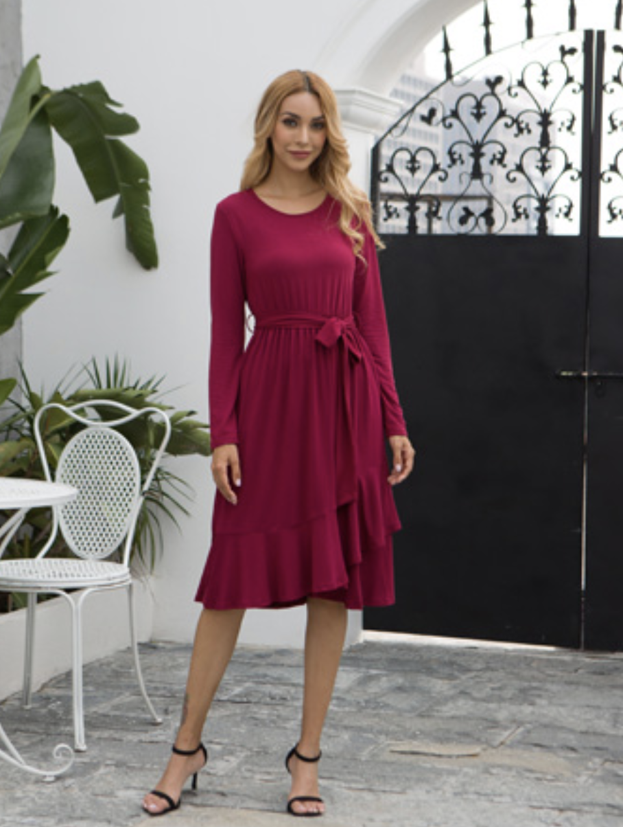 Model in a red long-sleeved tie-waisted dress
