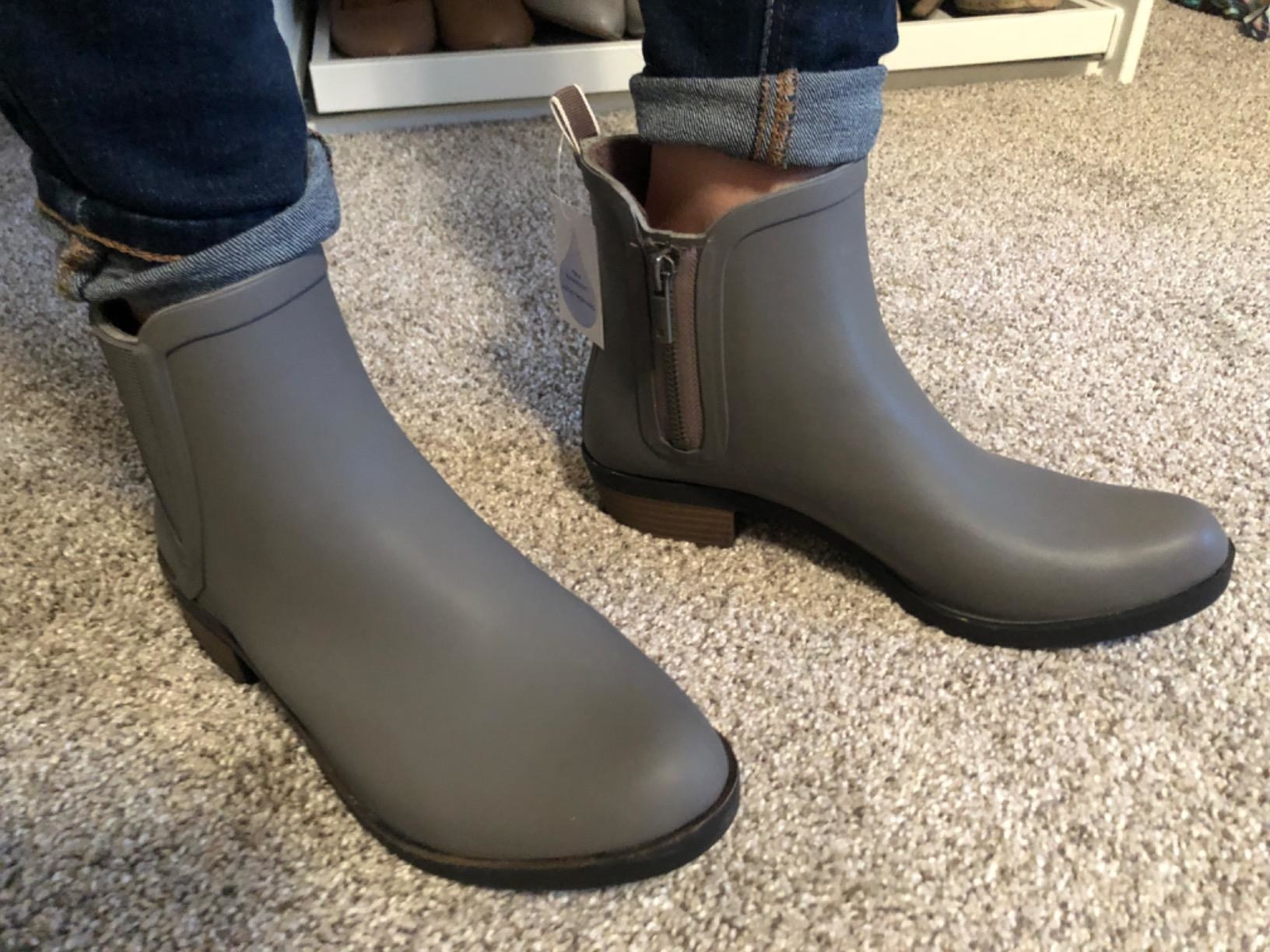 A reviewer wearing the ankle-length rubber boots in gray with a zipper on the side