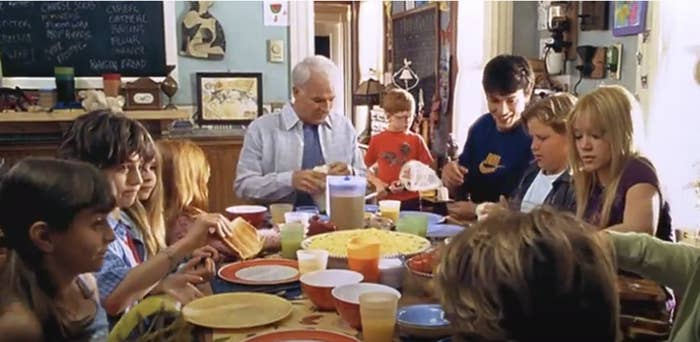 The Baker family, all fourteen of them, eat around a breakfast table