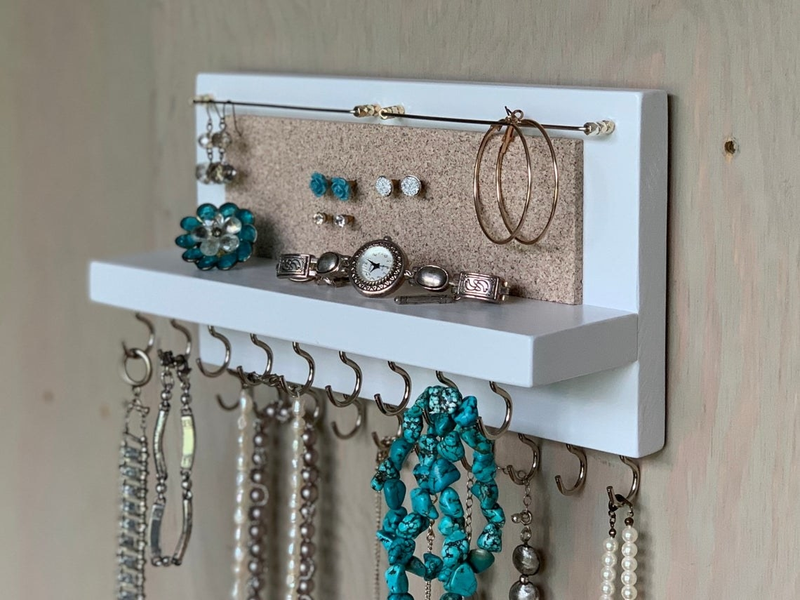 The organizer in white; it's a short plank of wood with a narrow shelf; there are two wires for dangly earrings above a cork panel for studs; beneath the shelf are two rows of nine hooks each, for necklaces and bracelets