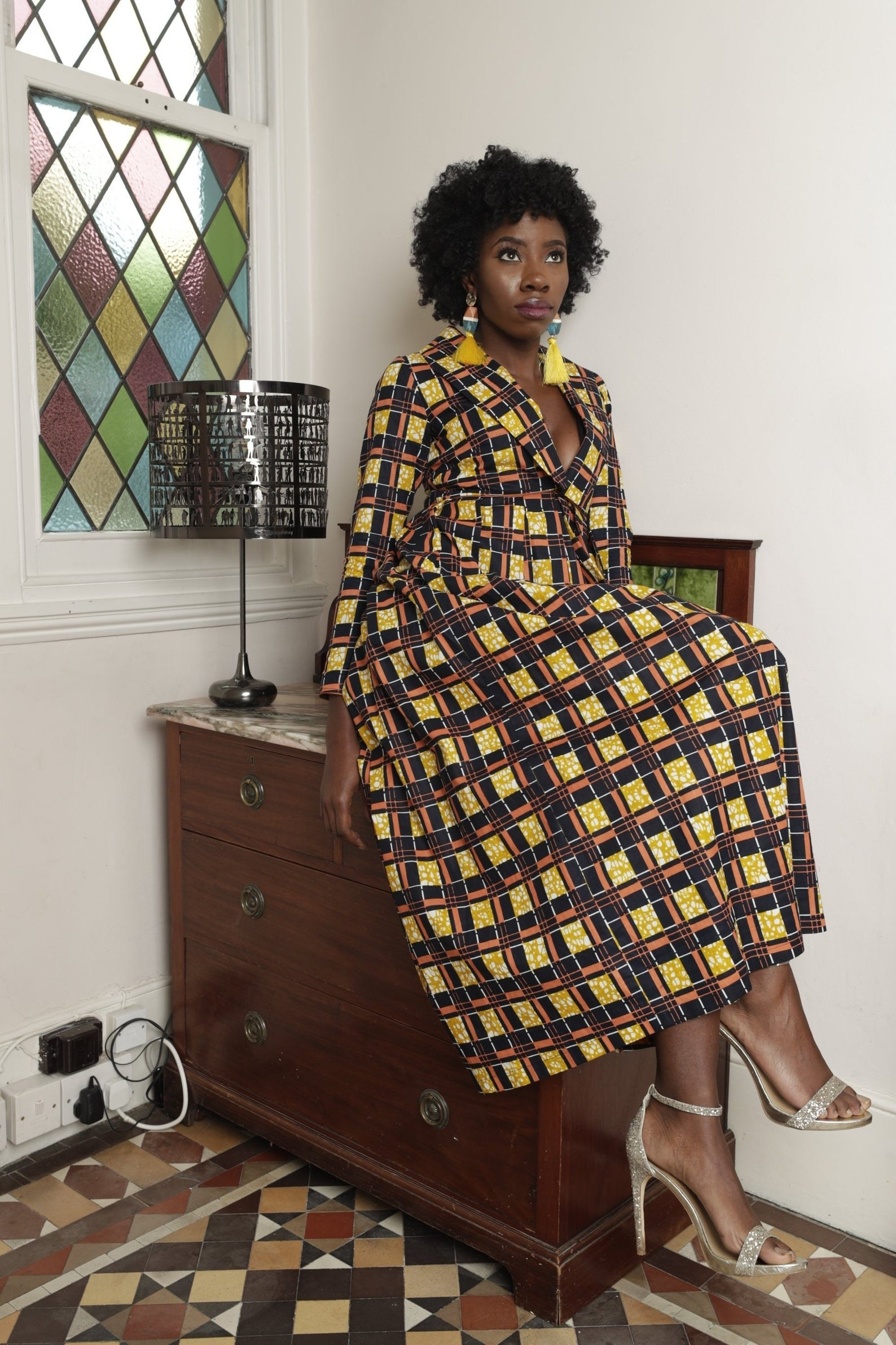 Model in a maxi dress with long sleeves in a yellow, navy, and orange African print