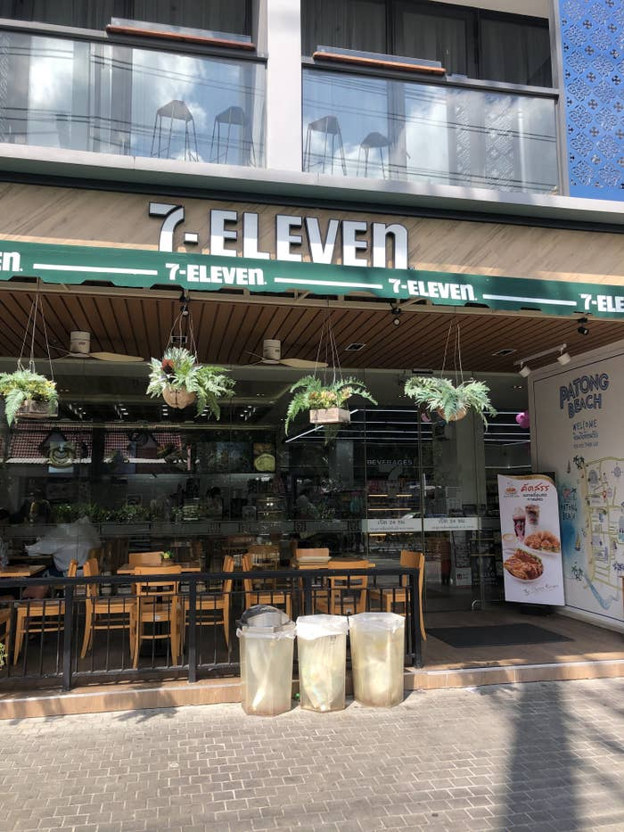 A fancy 7-11 store in Thailand with outdoor seating and plants