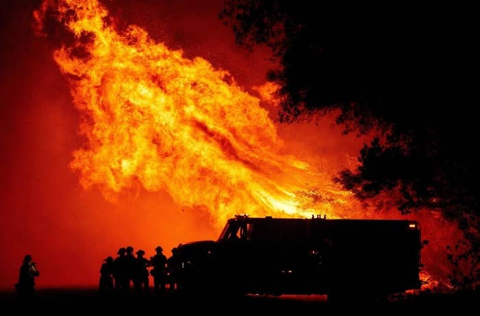 A large blaze towers overhead as five firefighters crowd by their truck