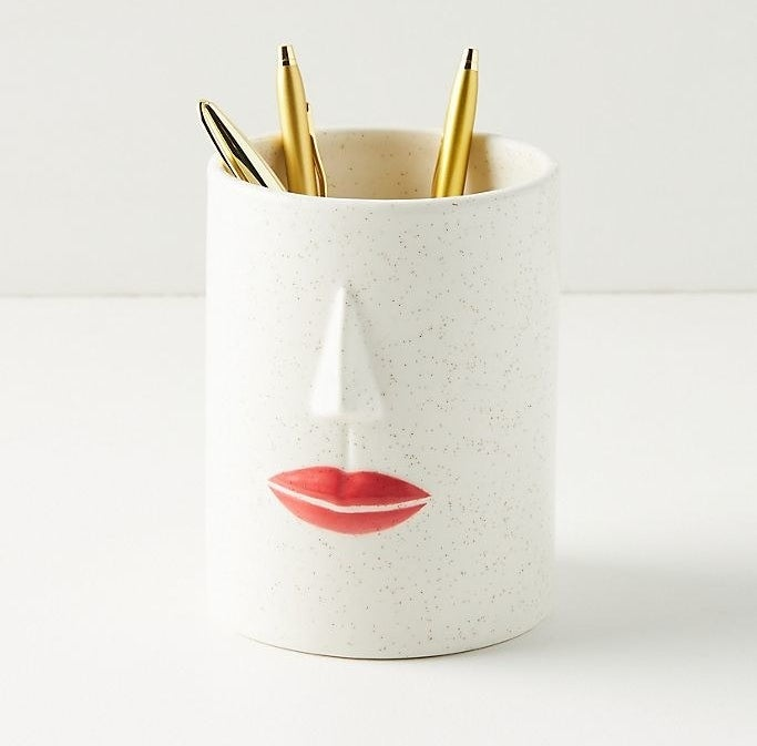 a white ceramic cup with a red lip print and nose to resemble face