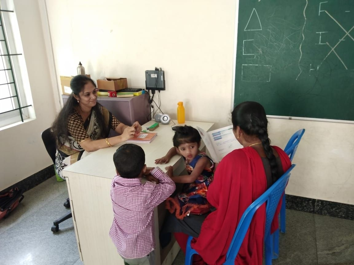 a mother, with a baby on her lap and the teacher smiling at her, looks at her kid's report card during a parent teacher meeting