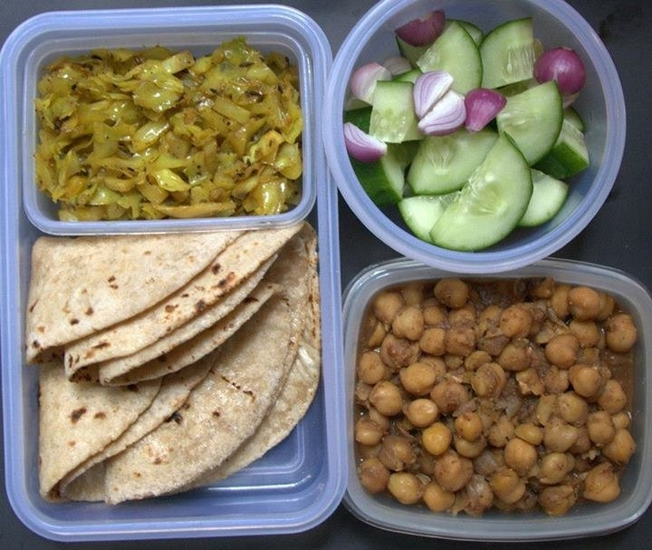 A plastic lunch box containing some roti, cabbage sabzi, chickpea sabzi and a salad of cucumber and onions