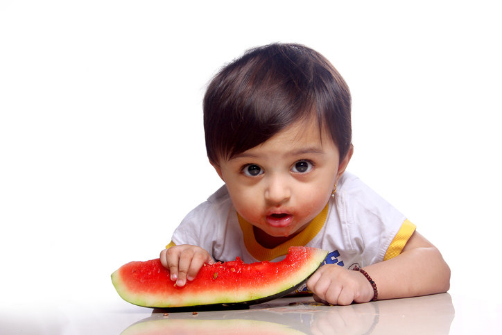 A small baby stares into the camera while eating a watermelon slice