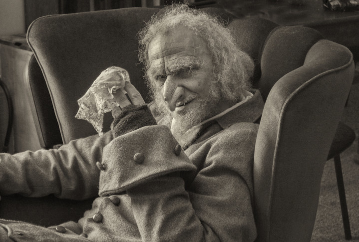 Black and white image of a mature man with long white hair, wearing scruffy clothes sitting in an old chair holding a white handkerchief