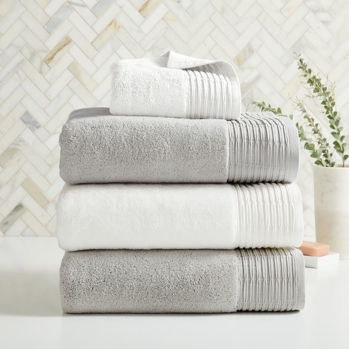 A stack of grey and white towels with pleated decorative edge