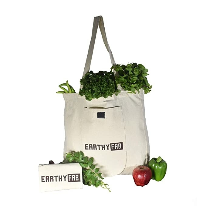 A cotton grocery bag filled with leafy greens and other vegetables.