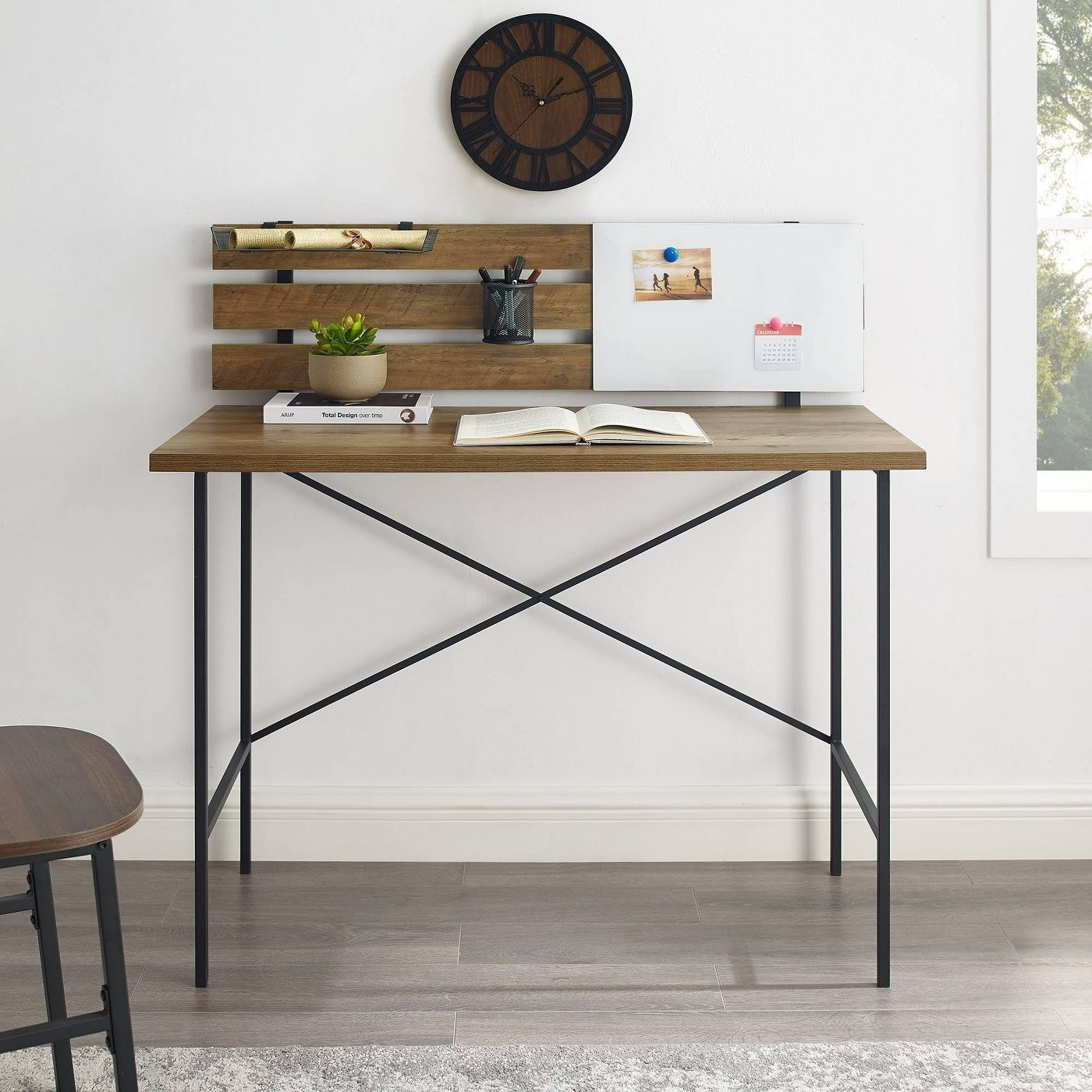 A wooden desk with black metal legs and a decorative packing against the wall for hanging photos or organizing items