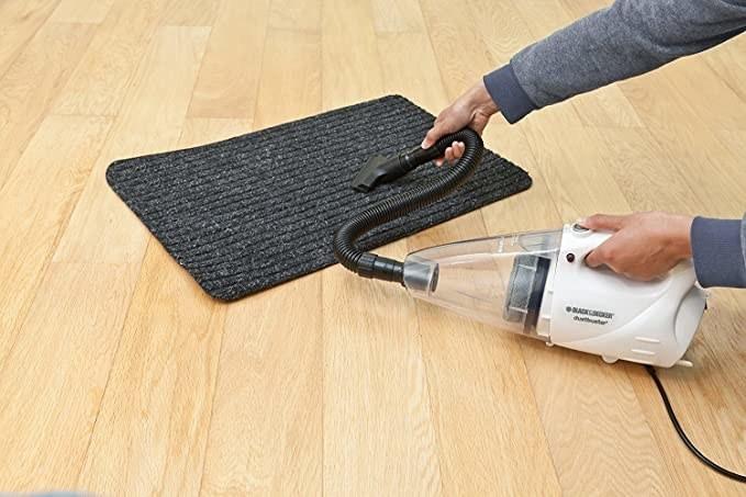 Vacuum cleaner cleaning a door mat.