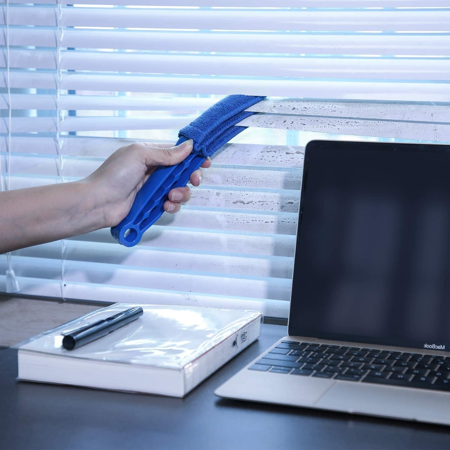 Model's hand using blue plastic and cloth duster brush on blinds