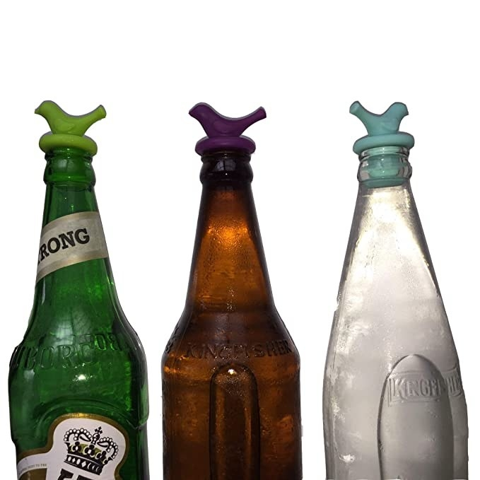 Three beer bottles with the beer stoppers closing  them.