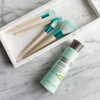 Light green colored bottle of makeup brush shampoo with gray top