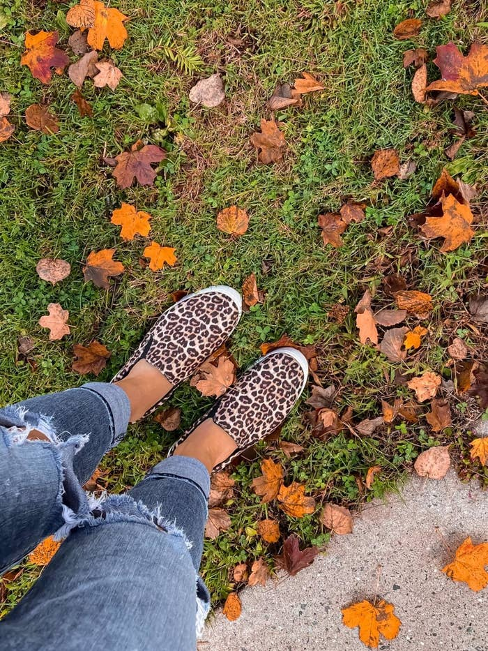 A reviewer standing on grass wearing their slip-on shoes with leopard print and white sole