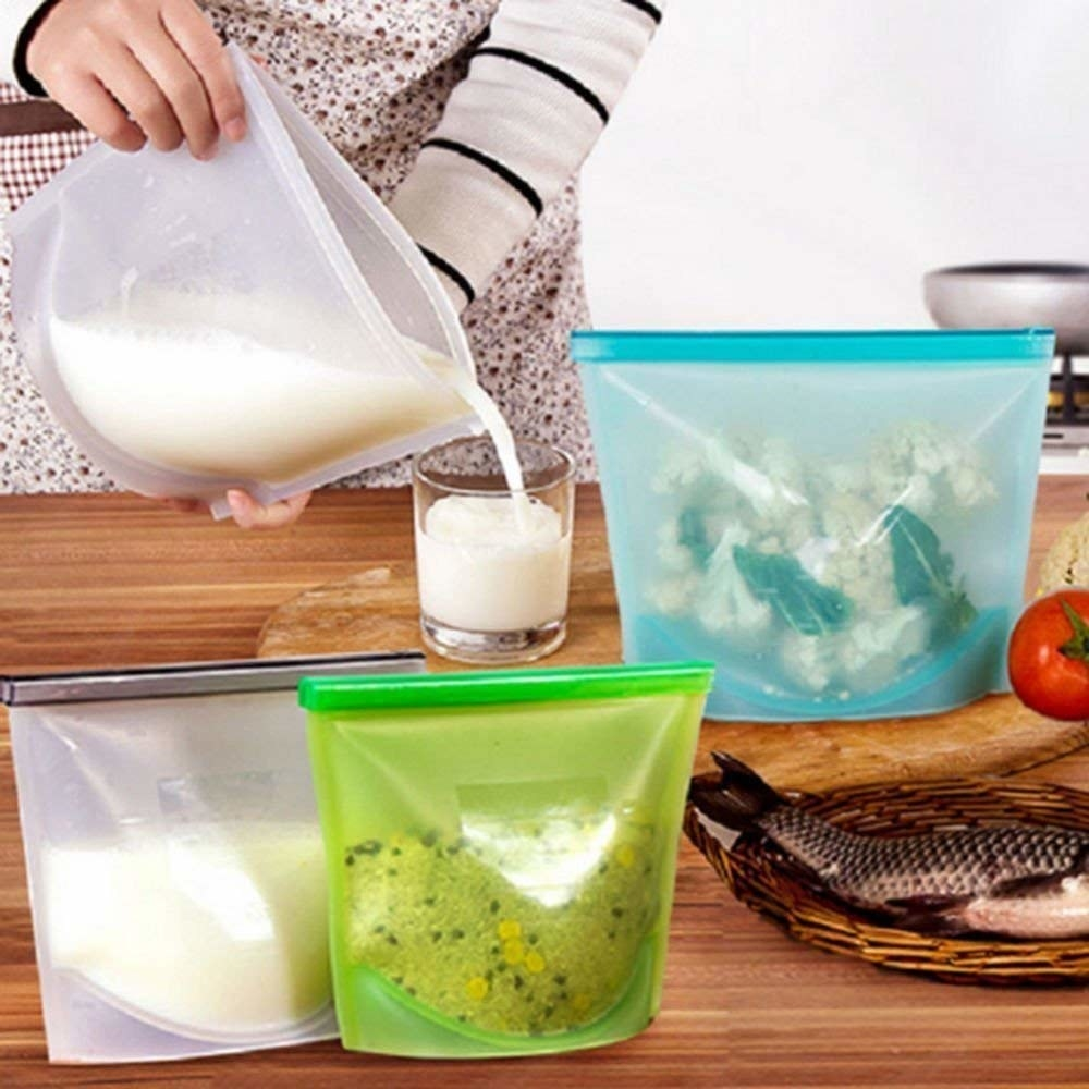 A hand pouring milk from a silicone bag into a glass and 3 other silicone bags with food stored in them.
