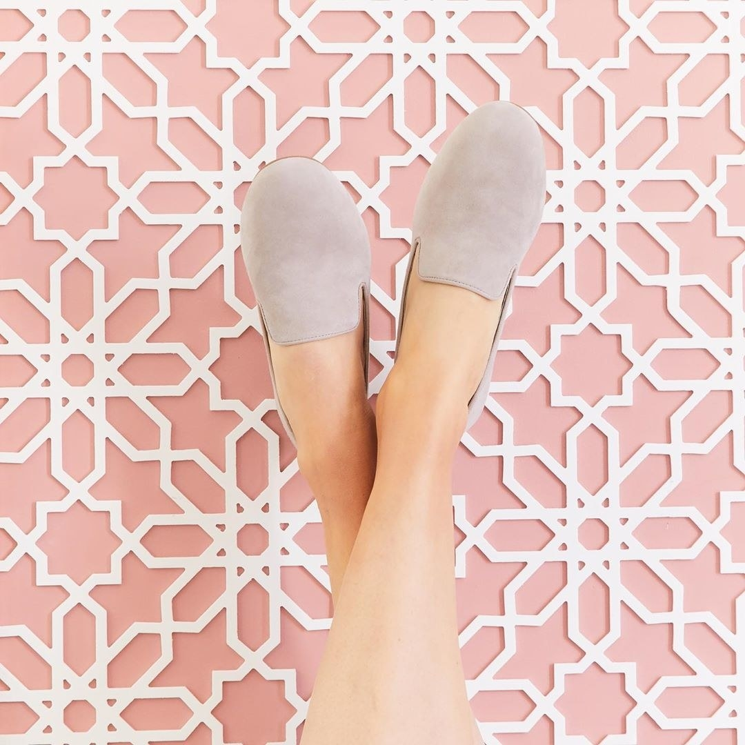 Model's feet up in the air with light grey suede flats