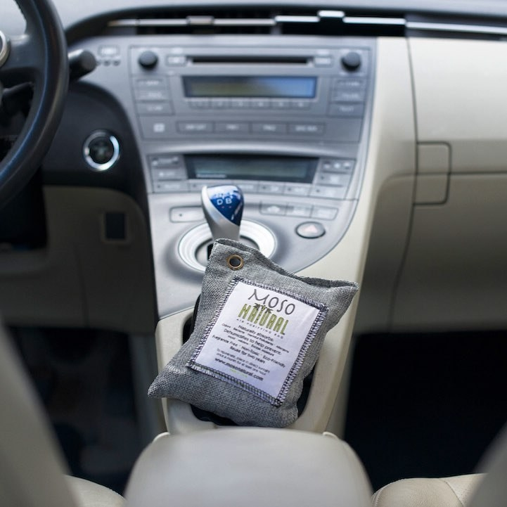 A small air purifying bag sitting on a car console
