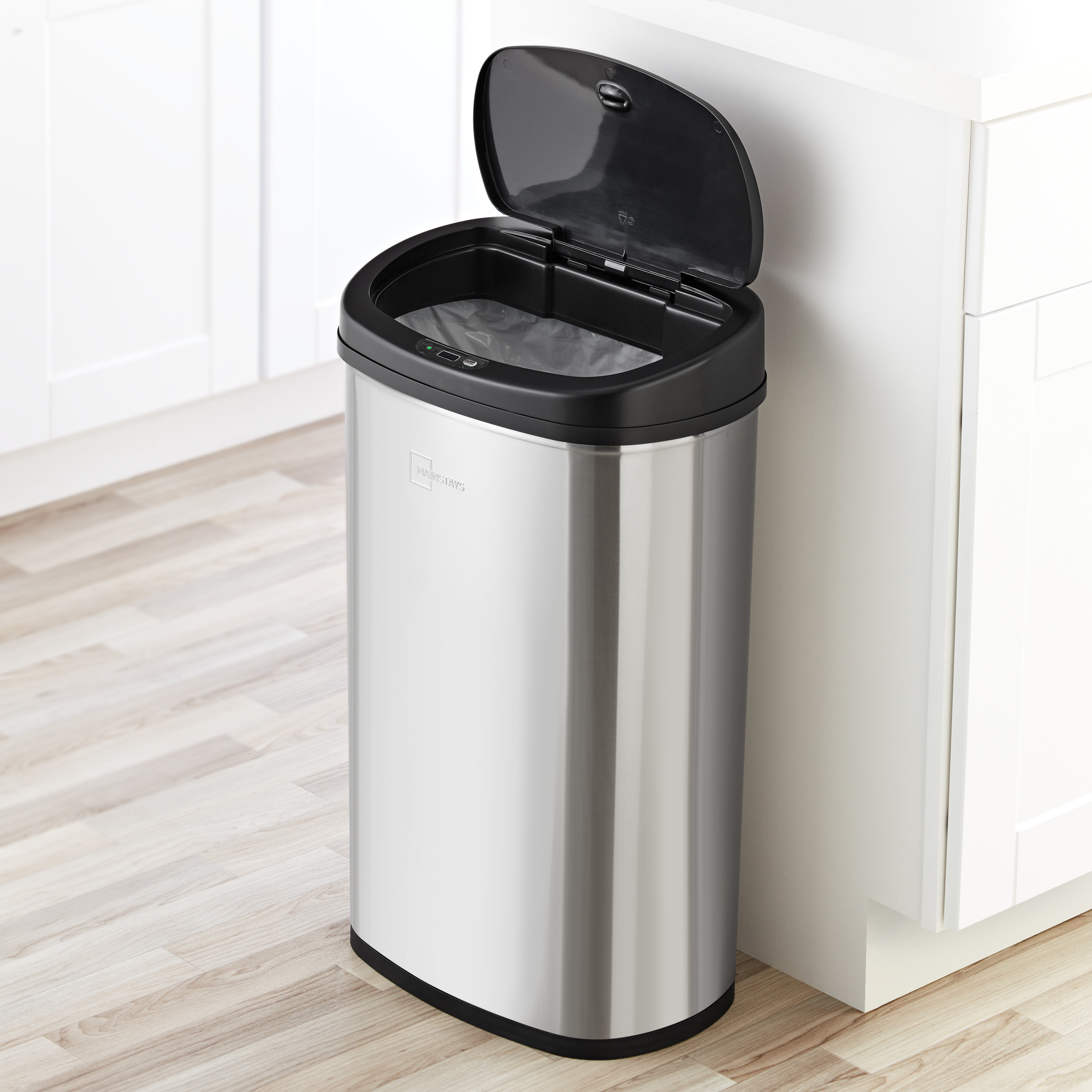 stainless steel motion activated trash can with the lid up in a kitchen
