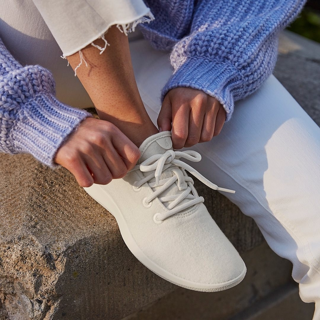 model tying white shoelaces on white sneakers