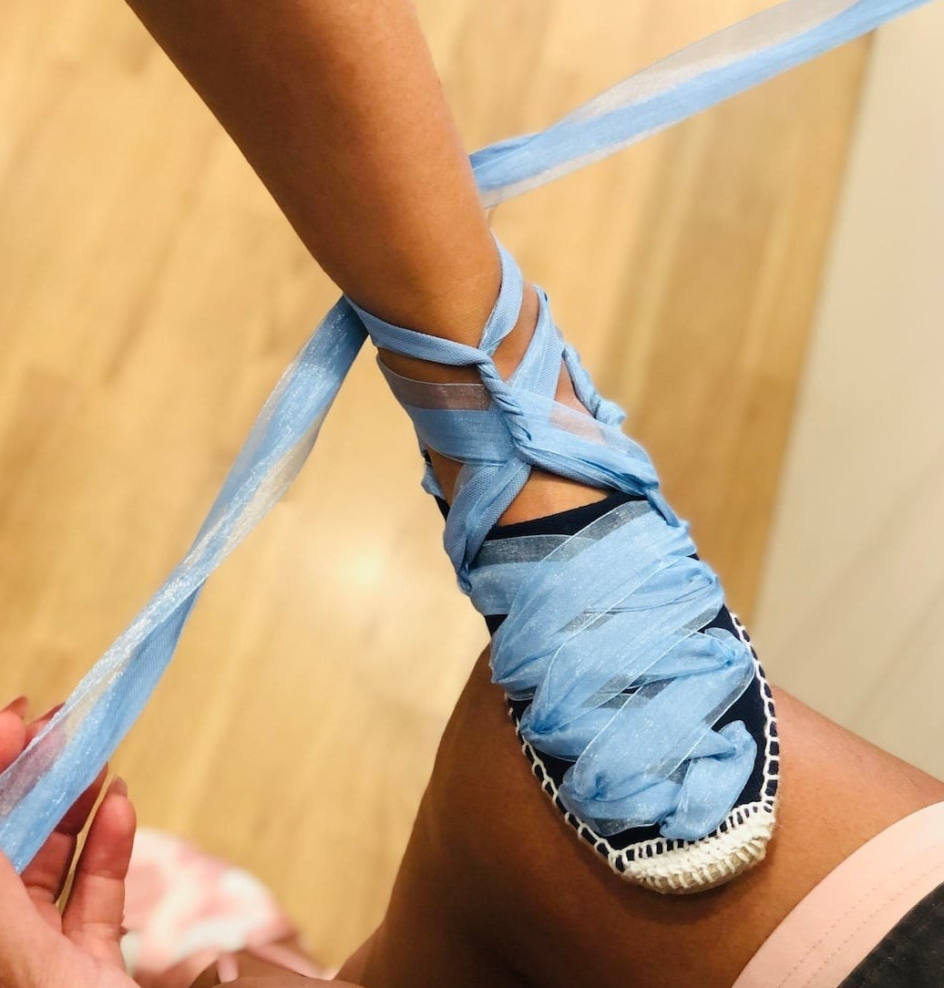 model tying blue laces on black espadrille shoe