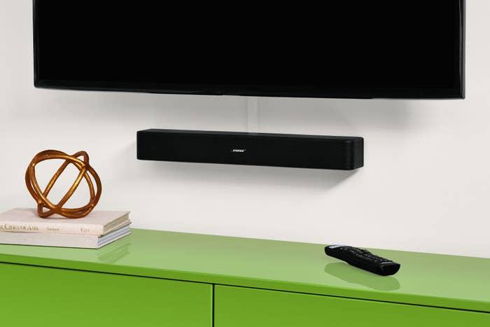 bose soundbar mounted underneath a tv on the wall