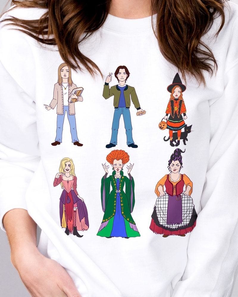 "model wearing white sweatshirt with illustrated ""Hocus Pocus"" characters"