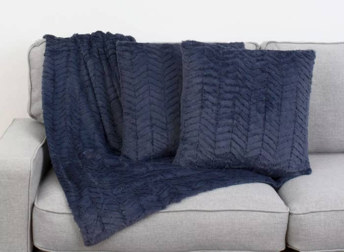 A navy throw blanket under two navy chevron throw pillows on a grey couch