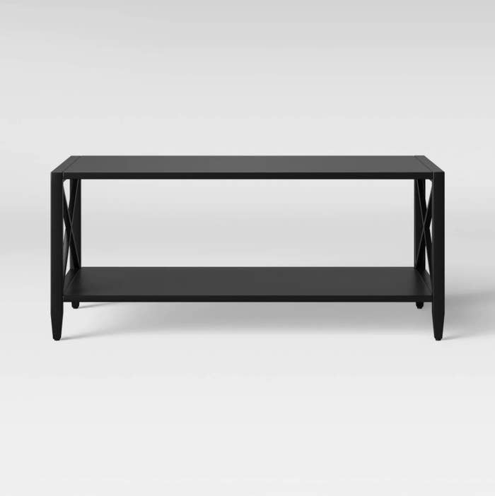 A black metal coffee table with cross beam designs on the side
