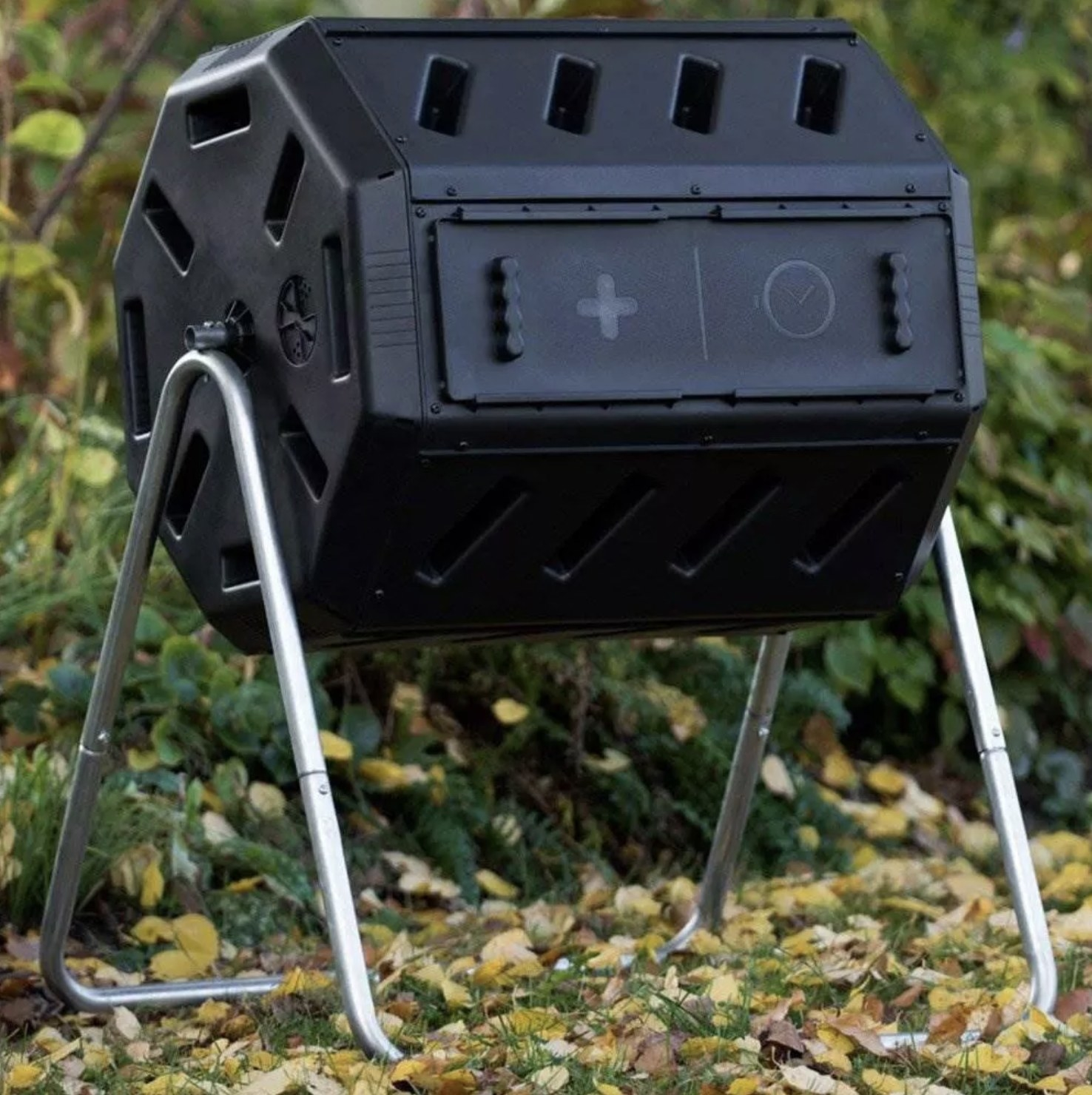 A black quick curing tumbling composting soil bin in a backyard