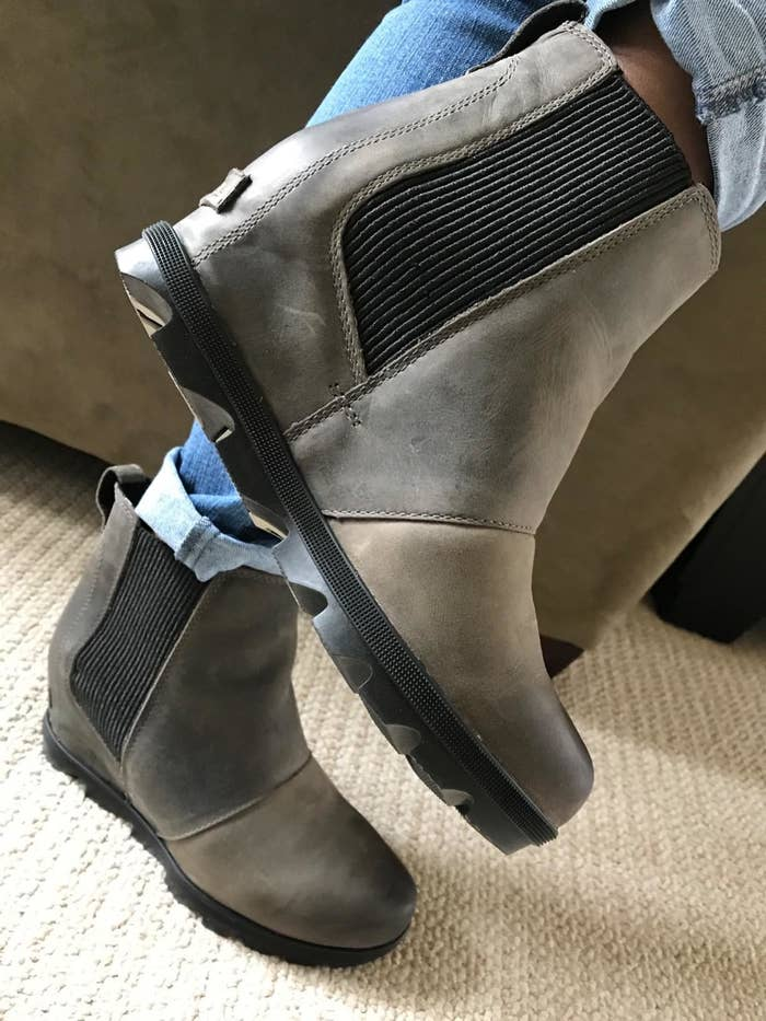 Reviewer wearing the wedge boots with wavy black sole with wide elastic section on either side