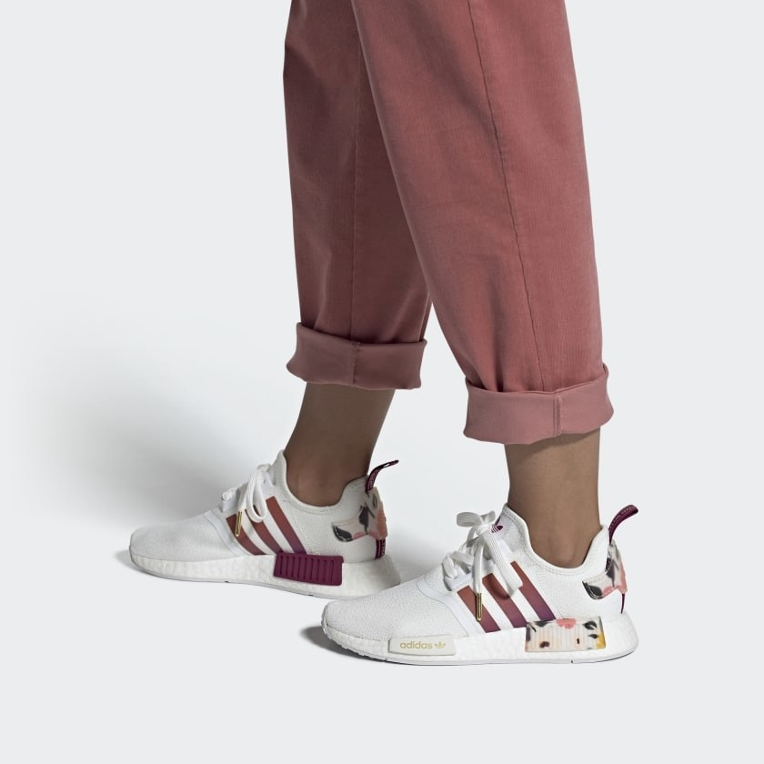 White sneaker with red stripes on the side and floral patches on the side and the heel.