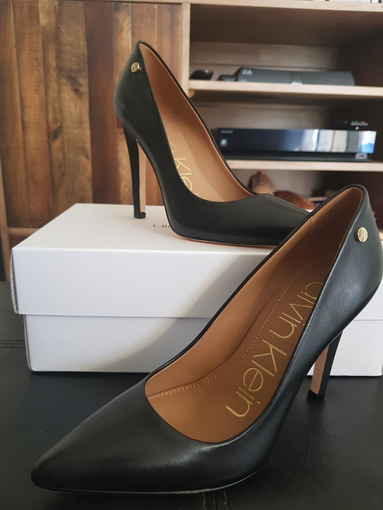 Reviewer photo of the black heels with a pointed toe sitting on top of and in front of the box