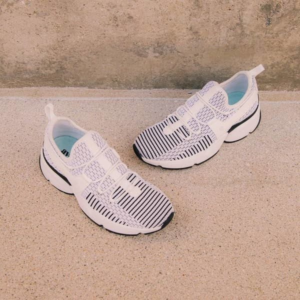 Knit sneakers with black stripes, criss-cross straps across the top, and chunky heels