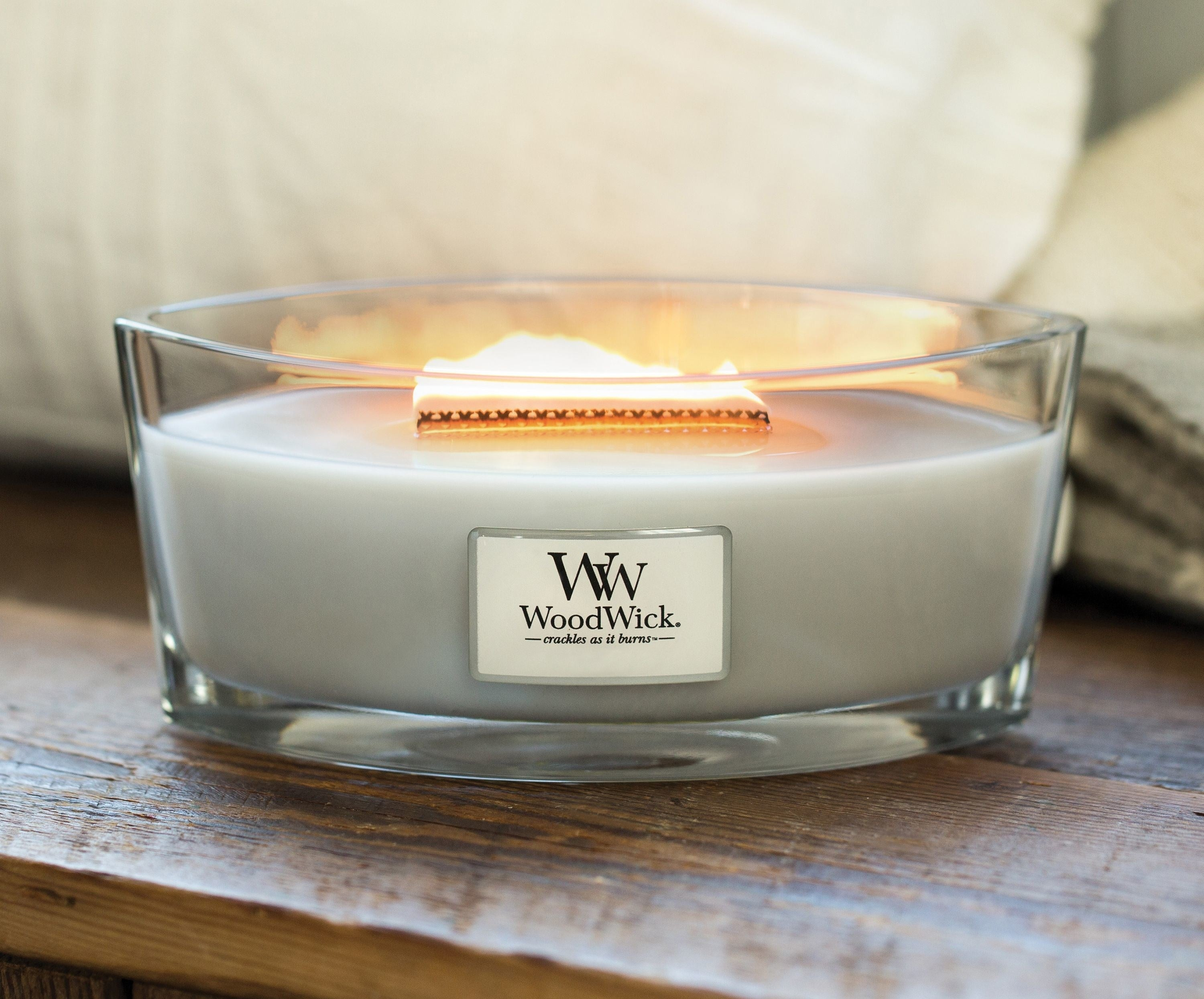 woodwick candle burning on wood counter