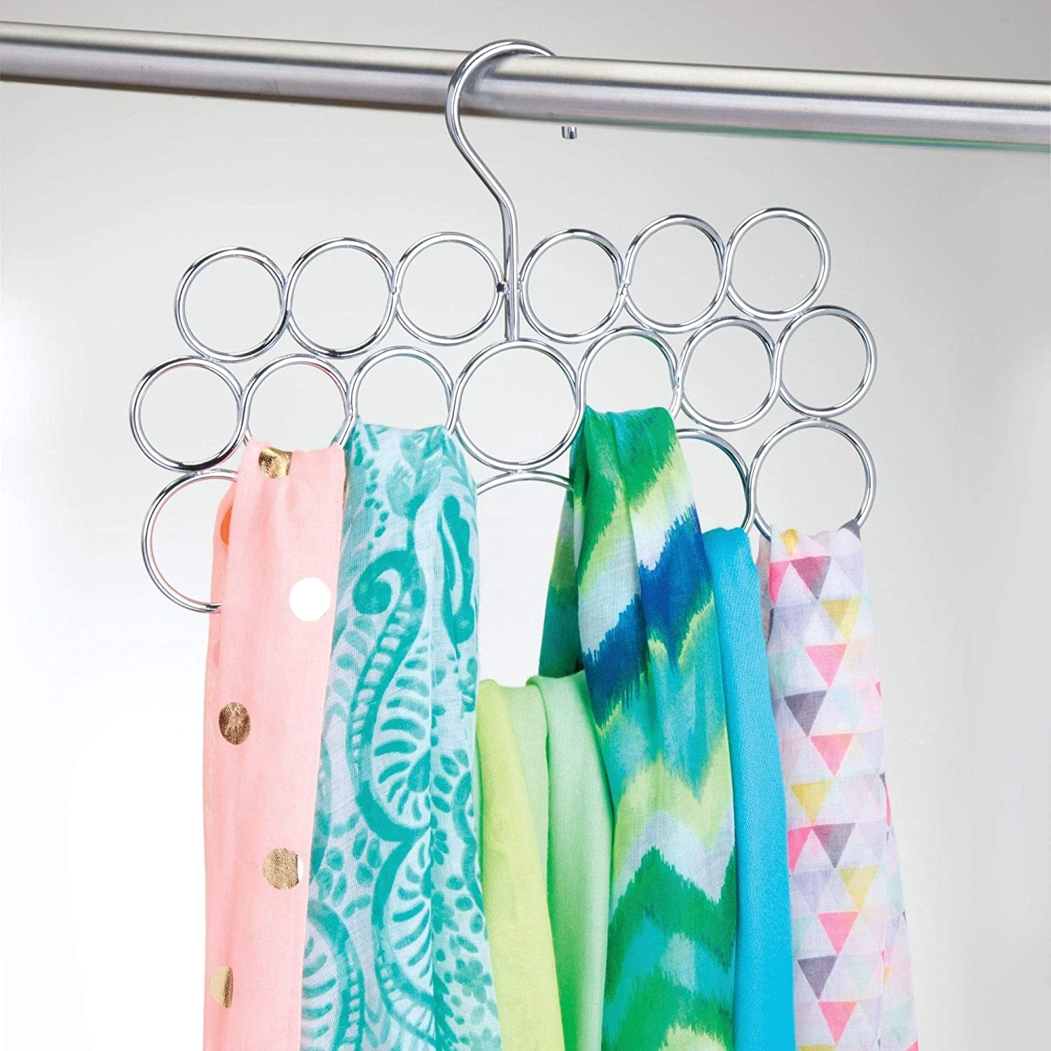 A metal hanger with a dozen small circles Colourful scarves are hanging from the loops