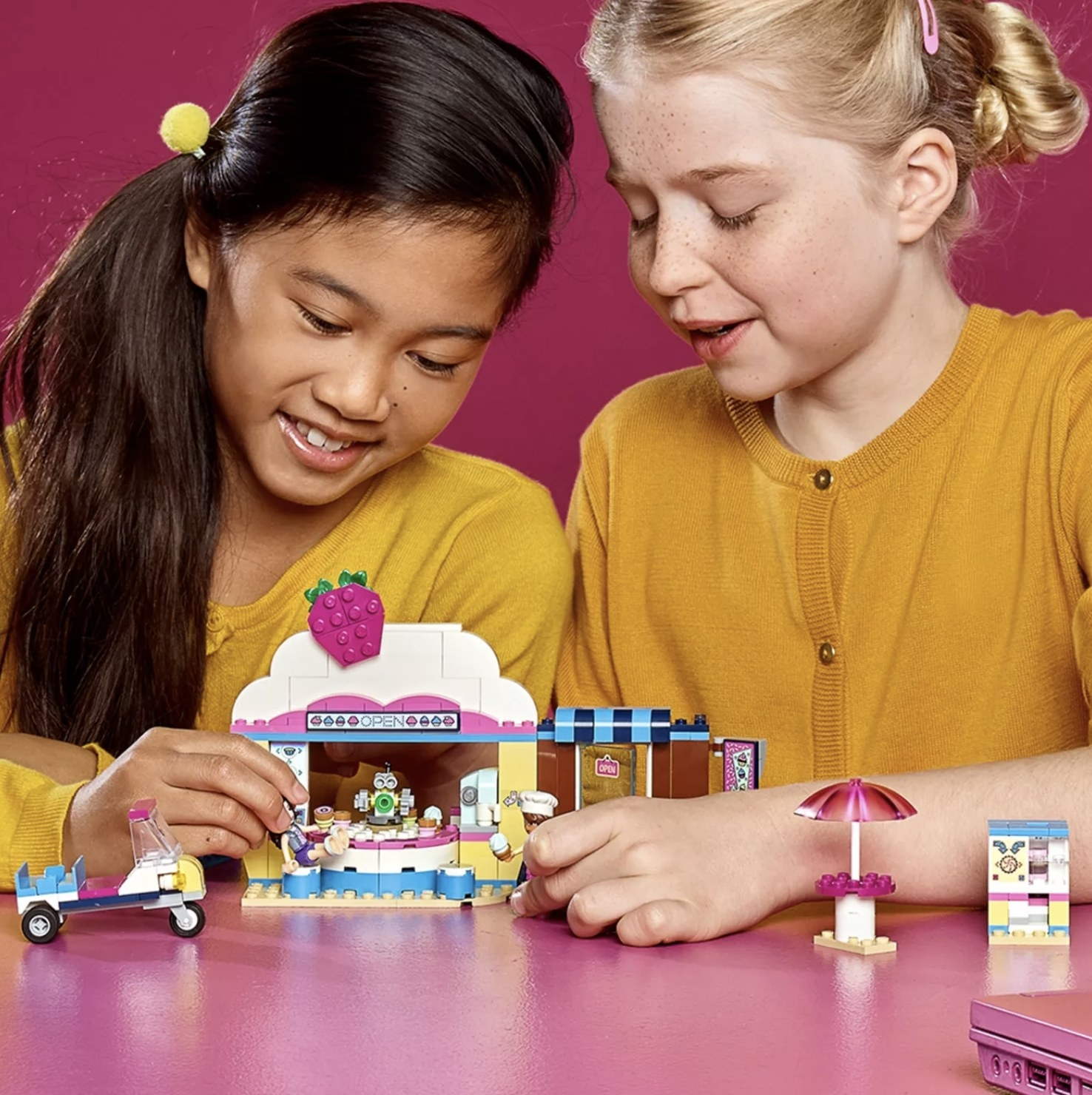 Two children are playing with LEGO Friends Olivia's Cupcake Café