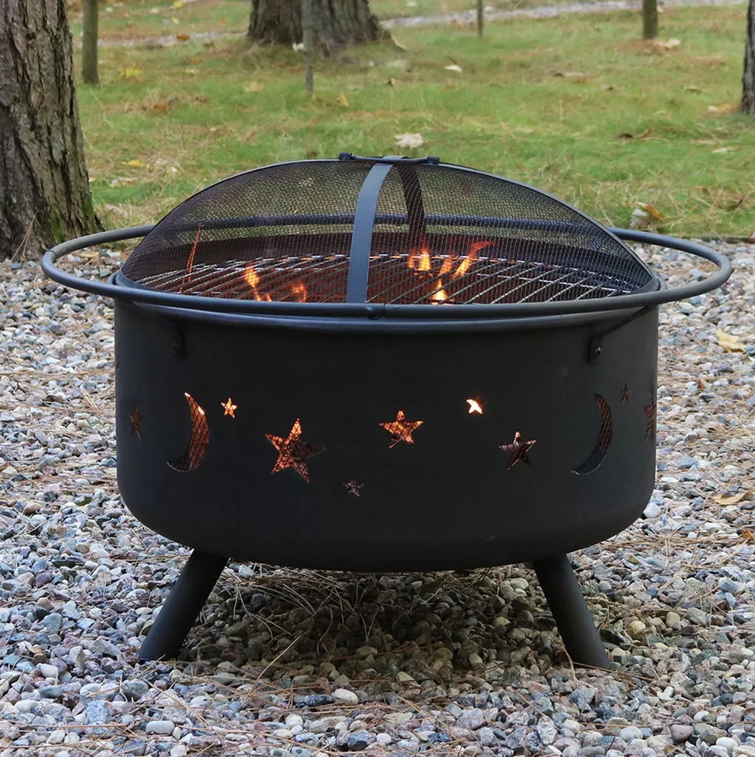 A wood-burning fire pit with a cooking grill is on with fire burning with a lid on top
