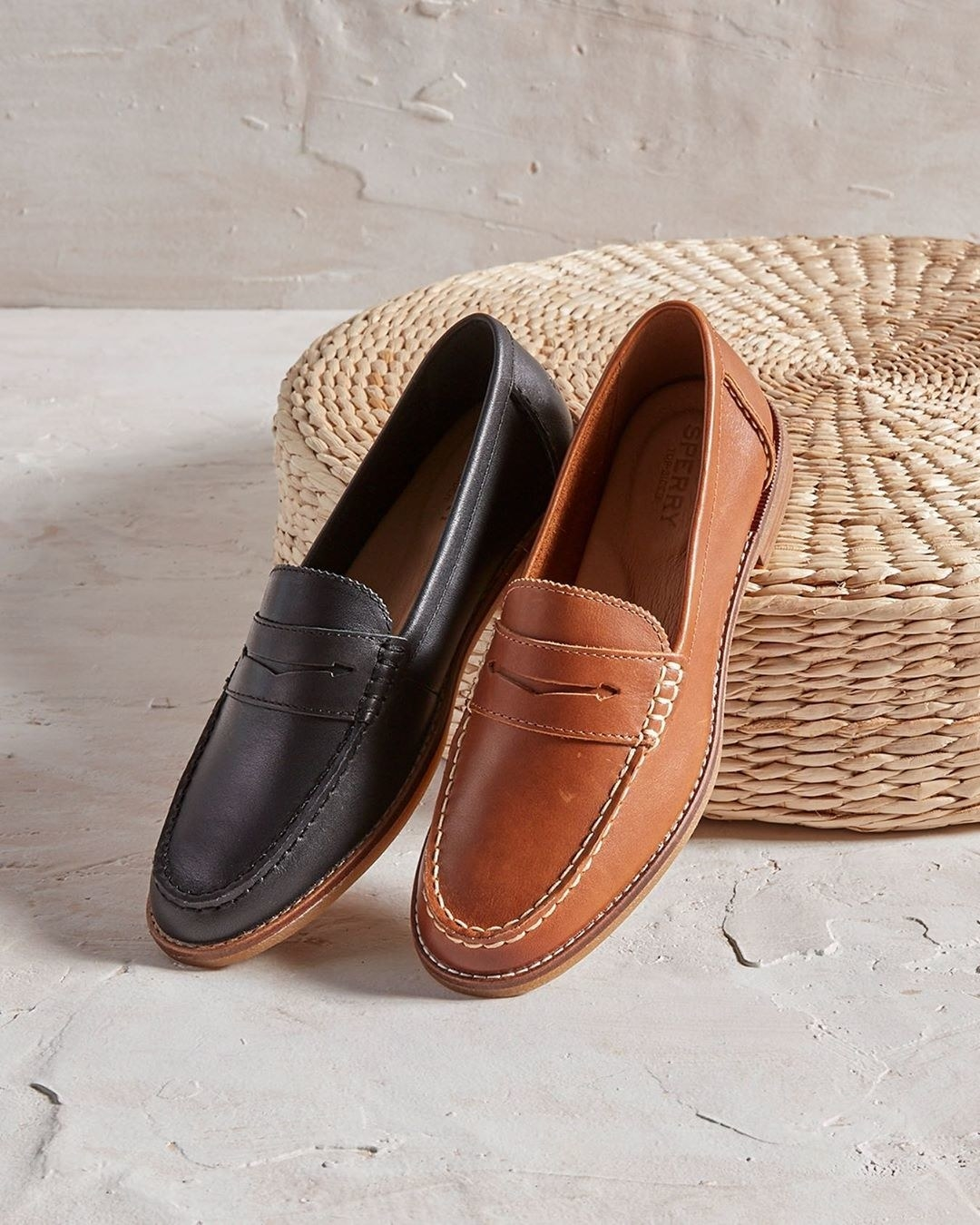 A black loafer and brown loafer sitting next to each other